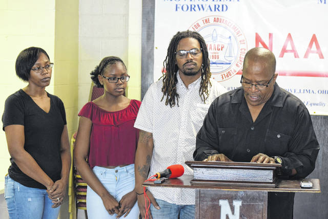 Rev. Ronald Fails (right) held a news conference Saturday to complain about a Lima Police officer's actions to break up a fight between two black teenage girls. One of them, Dymin Stephenson (second from left) was present with her parents at the event.