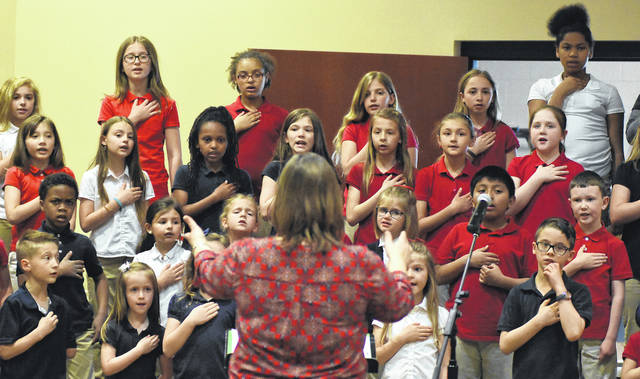 Music teacher Melinda Smith directs the Temple Christian Elementary School Choir in the Pledge of Allegiance during the National Day of Prayer event held at the UNOH Event Center on Thursday.