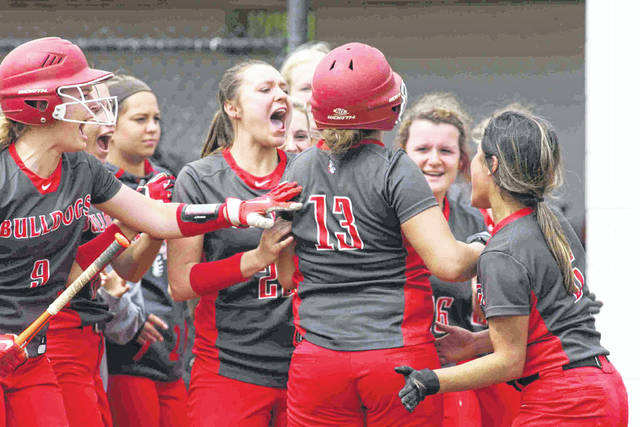 Columbus Grove's Teyah Sautter is mobbed by her teammates after hitting a home run in the first inning at the Division IV district championship game at Elida Saturday.