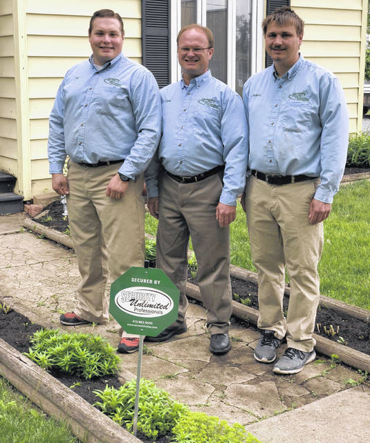 Joseph Ball, John Yohe and Randall Eads stand in front of a client's house in Lima.