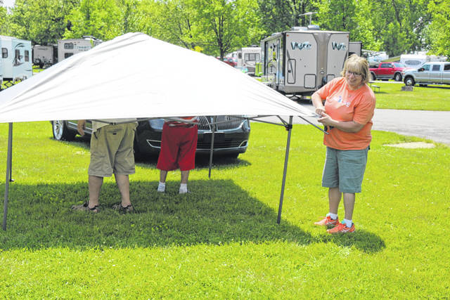 Leah Mattise from Clarkston, Michigan helps set up a dining fly at the family's campsite at Grand Lake St. Marys State Park. For many, this weekend marks the unofficial start of summer.