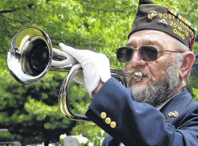 James Smith, a member of Lima VFW Post 1275, plays during a burial ceremony of World War II veteran William Spacer of Lima at Gethsemani Cemetery.
