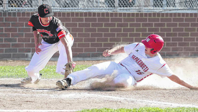 Wapakoneta's Manny Vorhees slides safe into home as Coldwater's Cole Frilling applies the tag on a passed ball in the bottom of the first inning at Wapakoneta High School Monday.
