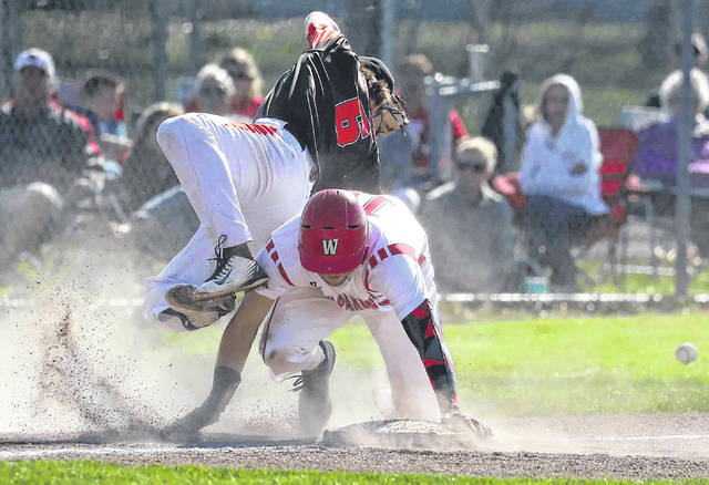 Wapakoneta's Brady Ebb upends Coldwater's Nate Grunden at third base as Ebb gets up and scores in the bottom of the second inning at Wapakoneta High School Monday.
