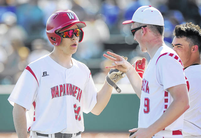 Wapakoneta's Don Goodes, left, is met by teammates Tuesday after scoring at Defiance.