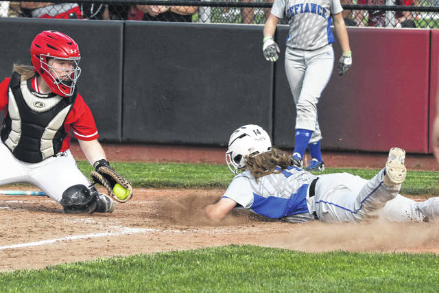 Defiance's Caroline Turner reaches home plate before Wapakoneta's Tianna Thompson can apply the tag during a Thursday night Division II district semifinal against Defiance at UNOH.