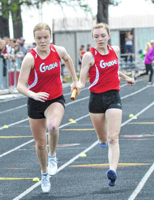 Columbus Grove Bulldog sprinter Lauren Benroth hands the baton to teammate Carlee McCluer in the 800 meter relay in the district three track meet at the Charles D. Moeller track in Spencerville.