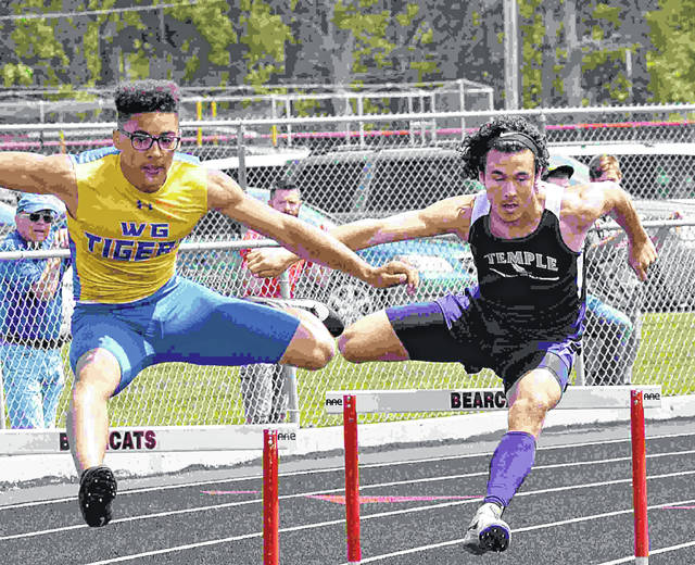 Waynesfield-Goshen Tiger Brandon James and Temple Christian Pioneer Cameron Worsham run the curve in the 300 meter hurdles in the district three meet at thr Charles D. Moeller track in Spencerville.