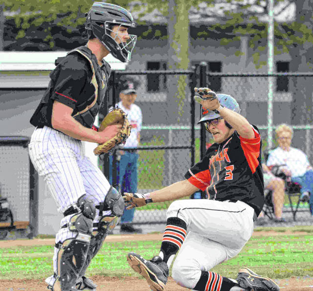 Elida Bulldog T. J. Whipple slides safely into home plate as Shawnee Indian catcher Jake Cowan watches the play on the field in a game at Ed Sandy Field.
