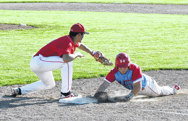 Lima Central Catholic's Sam Santaguida dives safely back to the bag against Hicksville's Braden Langham during a Thursday regional semifinal at Patrick Henry High School.