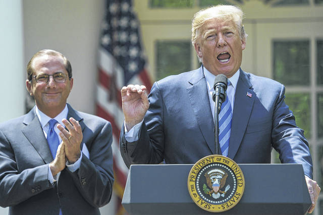 President Donald Trump speaks during an event about prescription drug prices with Health and Human Services Secretary Alex Azar, left, in the Rose Garden of the White House in Washington, Friday, May 11, 2018.