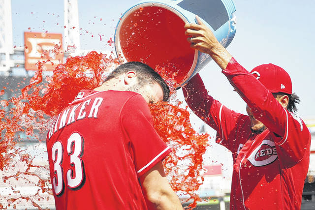 The Reds' Jesse Winker is doused by Luis Castillo after hitting a walk-off two-run home run in the 13th inning of Thursday's game in Cincinnati.