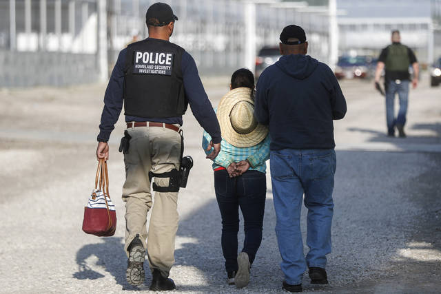 Government agents take a woman suspected of living in the country illegally into custody during an immigration sting at Corso's Flower and Garden Center in Castalia, Ohio, Tuesday, June 5, 2018. The operation is one of the largest against employers in recent years on allegations of violating immigration laws. (AP Photo/John Minchillo)