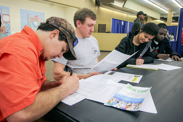 FILE- In this Feb. 8, 2018, file photo, Garrett Thornton, left, Bradley Harper, Heather Wood and Marcus Brown fill out various job applications at the Governor's Job Fair in the Tommy E. Dulaney Center in Meridian, Miss. On Tuesday, June 5, the Labor Department reports on job openings and labor turnover for April. (Paula Merritt/The Meridian Star via AP, File)