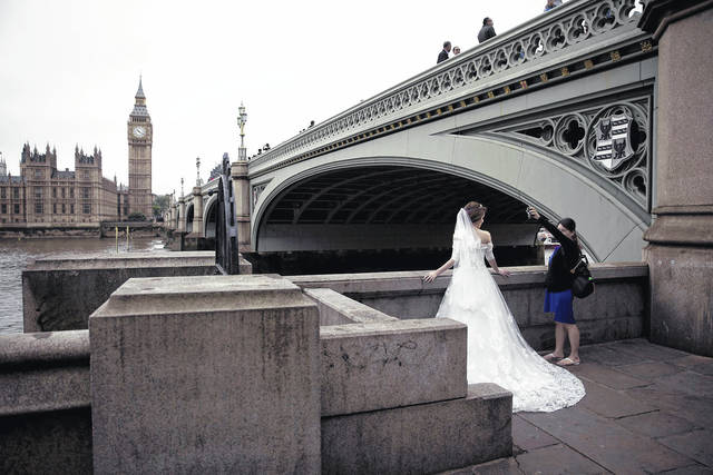 In this June 22, 2016, file photo, a woman assisting a photographer takes a light meter reading by the bride during a photo shoot for a Malaysian couple after they got married, backdropped by the Houses of Parliament on the opposite side of the River Thames in London. Planning a destination wedding abroad can be stressful for both you and your guests. The better prepared you are to navigate the variables, including legal requirements and possible language barriers, the easier it will be to bring your vision of the big day to life.