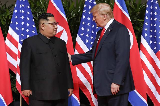 U. S. President Donald Trump greets North Korea leader Kim Jong Un at the Capella resort on Sentosa Island Tuesday in Singapore.