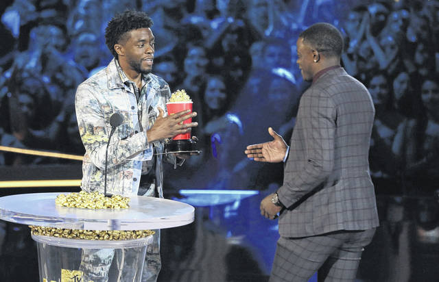 "In this Saturday, June 16, 2018, photo, Chadwick Boseman, left, gives his best hero award for his role in ""Black Panther"" to James Shaw Jr., who is credited with saving lives during a shooting at a Waffle House in Antioch, Tenn., at the MTV Movie and TV Awards at the Barker Hangar in Santa Monica, Calif. (Photo by Matt Sayles/Invision/AP)"
