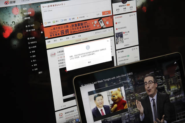 """A screen shows a failure message saying a post could not be sent because """"the content contains information that violates relevant laws and regulations"""" on Sina Weibo next to a smaller computer screen showing a """"Last Week Tonight"""" HBO show's host John Oliver with a photo of Chinese President Xi Jinping and Winnie the Pooh, in Beijing, Friday, June 22, 2018. The popular Chinese social media site is blocking users from posting about the show and its HBO host Oliver after the news satire program aired a segment this week making fun of Xi. (AP Photo/Andy Wong)"""