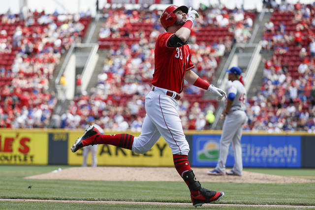 Cincinnati Reds' Jesse Winker (33) runs the bases after hitting a three-run home run off Chicago Cubs relief pitcher Pedro Strop, right, in the seventh inning of a baseball game, Sunday.