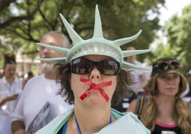 Deborah Campbell, dressed as the Statue of Liberty with red tape over her mouth, attends the Families Belong Together rally at the Capitol in Austin, Texas, on Saturday. Thousands gathered at the Capitol to protest family separations on the border.