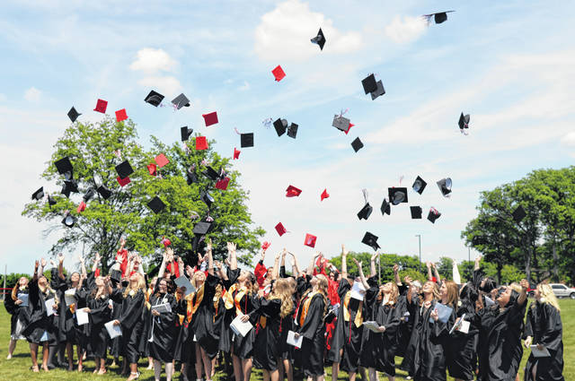Spencerville graduates throw their hats into the air after graduation.