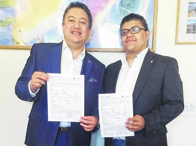 In this Tuesday, June 26, 2018 photo provided by David Quiroa, father David Quiroa, left, and son David Quiroa, Jr., right, hold their candidacy papers in Newport, R.I. The father will run as a Republican and the son will run as an independent in the November general election for the seat currently held by Democratic Rhode Island State Rep. Marvin Abney.