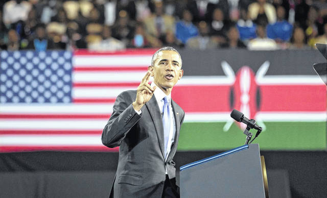 FILE - In this July 26, 2015 file photo, President Barack Obama delivers a speech in front of U.S. and Kenyan flags at the Safaricom Indoor Arena in the Kasarani area of Nairobi, Kenya. On Friday, June 29, 2018, The Associated Press has found that stories circulating on the internet that Obama visited his father's birthplace on a secret trip to Kenya in June 2018 are untrue.