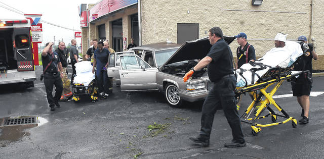 American Township EMTs and firefighters help the driver and passenger of a car that struck the Valvoline Instant Oil Change flagpole and building on Elida Road Friday morning.
