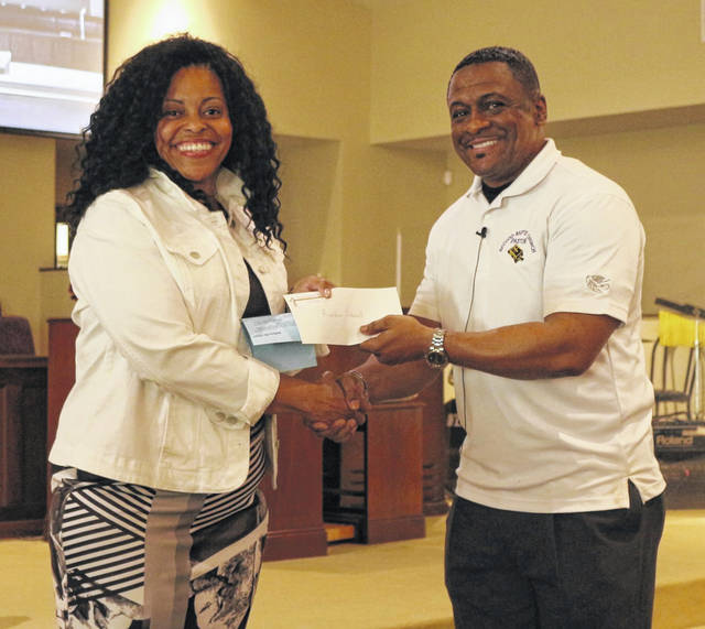 Lisa K. Bradley (left) Freedom School Site Coordinator for the Children's Defense Fund receives a $1,000 check from Pastor Dennis Ward, president of the Lima Area Black Ministerial Alliance.