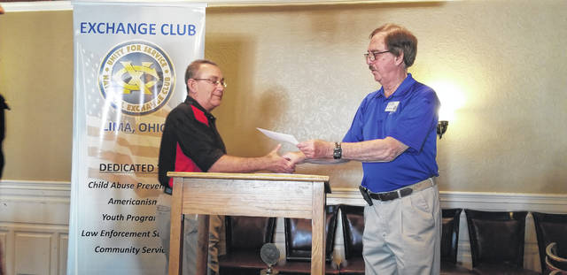 Lima Exchange Club President Mike Mullen presents Allen County Sheriff Deputy Mike White with a $1,000 check for the Allen County DARE program during a meeting Monday at Milano Cafe.