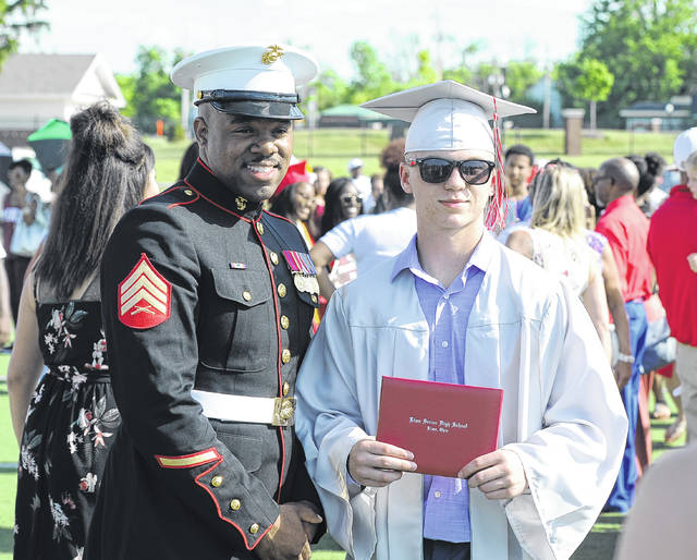 A student poses for a photo after Lima Senior's graduation.