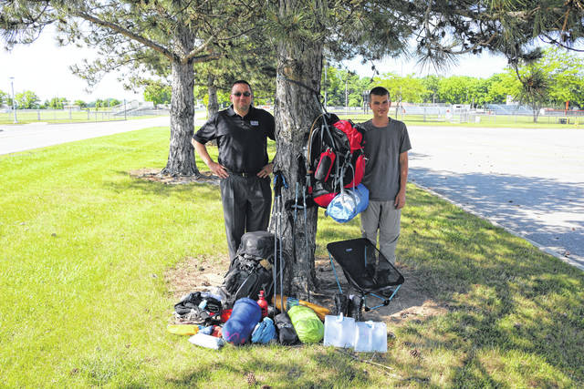 Chad Bryan, Assistant Scoutmaster for Boy Scout Troop 84 from Gomer, poses with his son Dylan with some of the equipment they were hoping to use at Philmont Scout Ranch in New Mexico. Wildfires have forced scout officials to cancel activities through mid-July.