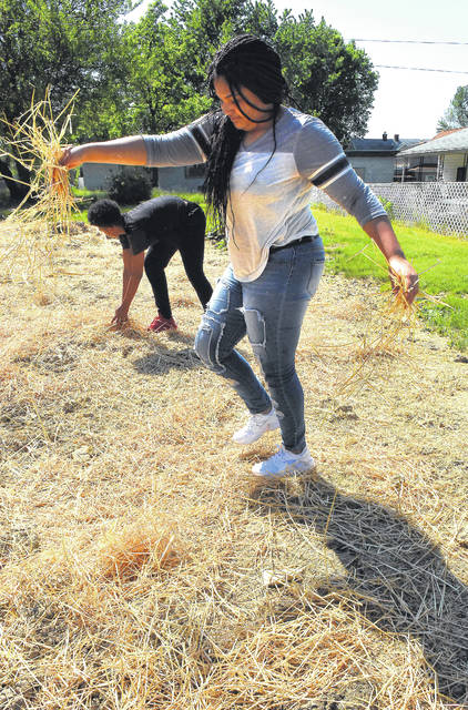 Jakyra Petty, 15, and her brother, Kylon, 13, straw an undeveloped lot on South Atlantic in Lima while working a summer jobs program.