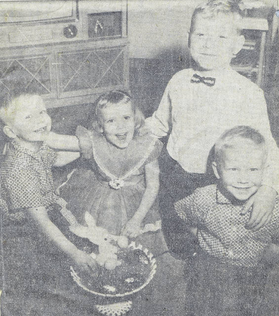"""This photo, published April 10, 1960, in The Lima News, shows four siblings who were celebrating April birthdays. They were the children of Mr. and Mrs. Norman Monfort. From left is Greg, 4, Kathy, soon to be 5, Eddie, 8, and Jeff, also 4. (Greg and Jeff are twins.) In the center, the family Easter basket symbolizes the children's birthday month. The Lima News staffer Bob Pendergast wrote a feature story on the family's birthday celebration, which included a big tour to visit all the grandparents. """"The Monforts are a typical Lima young couple who seem to be growing up with their blonde haired, blue eyed youngsters and 'although Norman and I don't have April birthdays, we get as much fun out of the big party as the kids,' says the mother. … The twins, who call each other Greg, forgetting that one is named Jeff, got cowboy suits for their birthday a week ago Saturday. Their sister wants a cowboy hat and boots next Saturday, when she makes the grade, and only Eddie's interest seems to turn to the sports' world. He got baseball equipment yesterday. That's the kind of present you'd expect on an April birthday."""""""