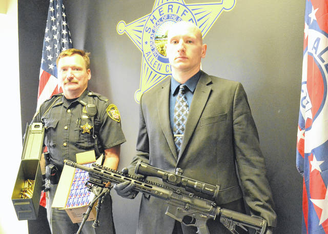 Detective Ryan Ream holds the confiscated AR-15 rifle and Lt. Kevin Litsey shows a box of ammunition. Bryan Reynolds | The Lima News