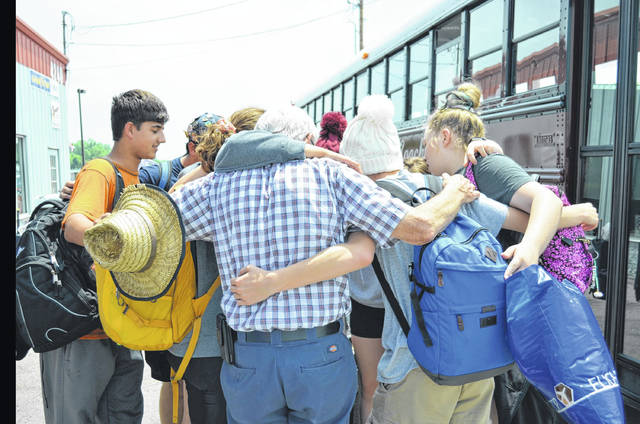 The student delegates with The Lima Sister Cities Association performs a group hug after returning home from Harima-Cho, Japan, Tuesday.