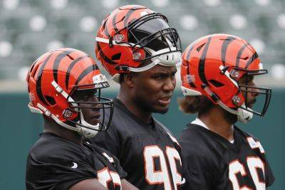 Bengals defensive end Carlos Dunlap, center, stands with his teammates Tuesday during practice at the team's training camp in Cincinnati. AP photo
