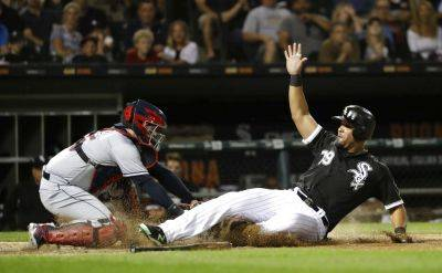 Chicago White Sox's Jose Abreu, right, avoids the tag of Cleveland Indians catcher Roberto Perez and scores on a single by Kevan Smith during the sixth inning of Wednesday night's game in Chicago. (AP photo)