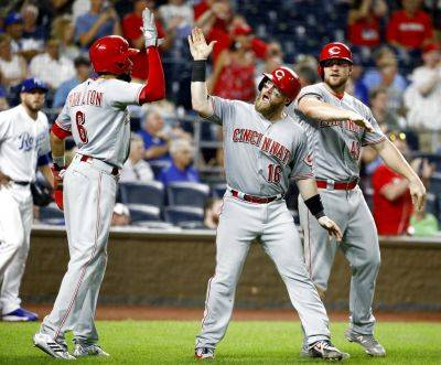 Cincinnati Reds' Billy Hamilton (6), Tucker Barnhart (16) and Scott Schebler celebrate after scoring on a three-run triple by Joey Votto during the 10th inning of a baseball game against the Kansas City Royals on Tuesday, June 12, 2018, in Kansas City, Mo. The Reds won 5-1 in 10 innings (AP Photo/Charlie Riedel)