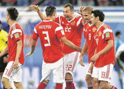 Scorer Artyom Dzyuba, center, and his teammates celebrate Russia's third goal Tuesday in a World Cup match against Egypt in St. Petersburg, Russia.