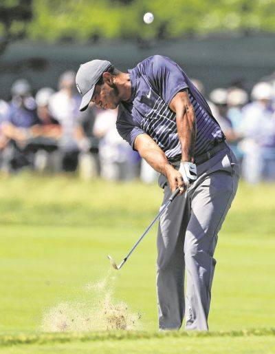Tiger Woods hits an approach shot on the fourth hole during Thursday's first round of the U.S. Open in Southampton, N.Y. AP photo