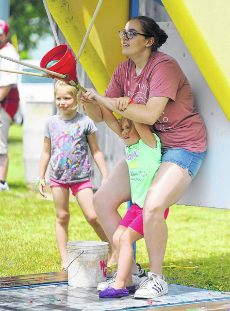 Maddilyn Helmin and Allison Howard play water wars during a past year's Pork Rind Heritage Festival in Harrod.