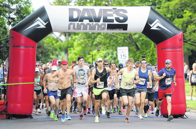 Race winner Dustin Sprague (1077) leads a pack of runners during Wednesday's Freedom 10K at Faurot Park.