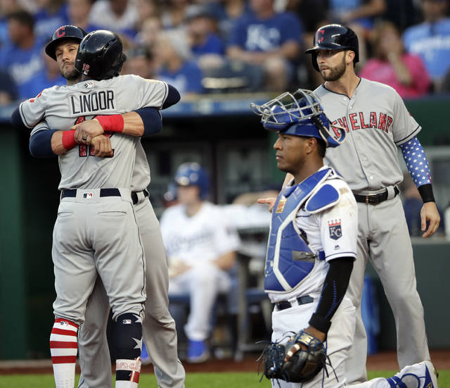 Cleveland Indians' Francisco Lindor (12) is congratulated by teammates Yan Gomes, left, and Tyler Naquin, right, after his grand slam during the fourth inning of a baseball game against the Kansas City Royals at Kauffman Stadium in Kansas City, Mo., Monday, July 2, 2018. Royals catcher Salvador Perez, second from left, waits for the next batter. (AP Photo/Orlin Wagner)