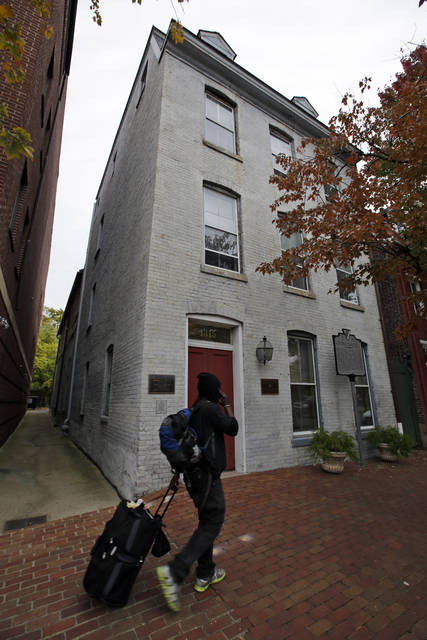 """FILE - This file photo taken Oct. 31, 2013 shows a person walking past the Freedom House Museum in Alexandria, Va. A historic preservation group is awarding $1.1 million to help support important African-American historic sites. Brent Leggs directs the African-American Cultural Heritage Action Fund, which is an effort by the National Trust for Historic Preservation. He says African-American historic places have traditionally """"been undervalued and underfunded."""" The fund will allow them to """"raise the visibility and the full contributions of African-Americans to our nation.""""  (AP Photo/Alex Brandon, File)"""