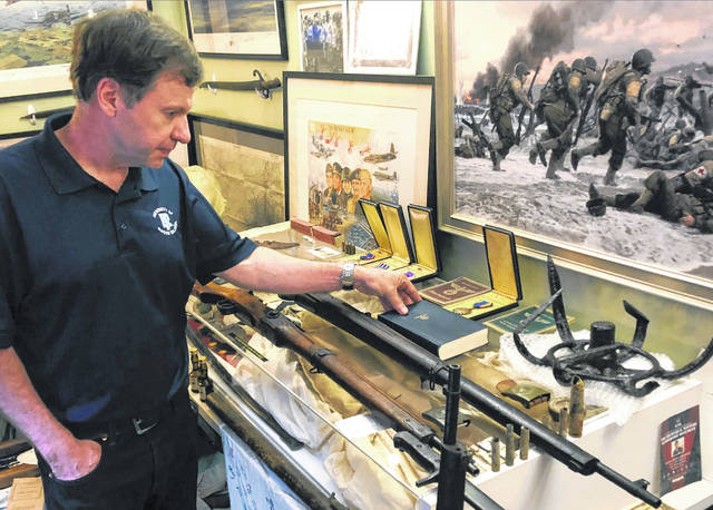 Filmmaker Tim Gray looks at books, medals and other items from World War II, some of the numerous items destined for a planned WWII education center in Wakefield, R.I. on June 22. Gray, founder of the nonprofit World War II Foundation, plans to open the center in September.