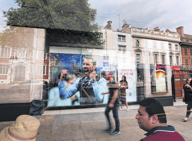 Seen with reflections through a bus shelter, the window of retailer Marks and Spencer store displays an image of England head coach Gareth Southgate in London, showing support for the England soccer team. The soft-spoken Southgate in a simple blue waistcoat seems to be uniting Britain amid dreams of victory in soccer's World Cup, with its next match against Croatia on Wednesday.