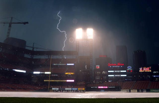 Lightning flashes in the distance as a thunderstorm passes over Busch Stadium during a rain delay in a baseball game between the St. Louis Cardinals and the Cincinnati Reds Saturday, July 14, 2018, in St. Louis. The rain delay was the second of the game. (AP Photo/Jeff Roberson)