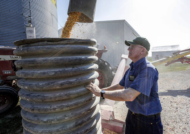 In this photo taken Thursday, farmer Don Bloss checks on the operation of an auger transferring corn on his farm in Pawnee City, Neb. Farmers and agricultural economists are worried that president Donald Trump's trade, immigration and biofuels policies will cost farms billions of dollars in lost income and force some out of business. Bloss, who grows corn, soybeans, sorghum and wheat on his farm in the southeastern Nebraska community of Pawnee City, said he's already seen a few neighbors quit farming as they struggled to make a profit even before the tariff battle began this year.