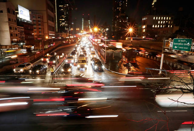 FILE- In this Jan. 11, 2018, file photo, cars pass the Queensboro Bridge in New York. The Trump administration is citing safety to justify freezing gas mileage requirements. A draft of a regulation prepared this summer would freeze an Obama-era program to improve fuel efficiency and cut pollution.